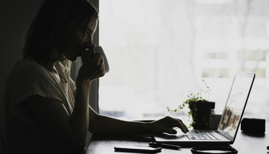 Kvinna med bärbar dator i mörker