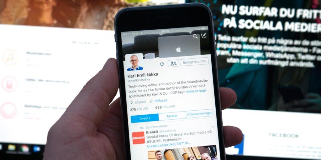 Mobil med Twitter-app framför dator