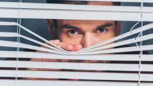Spion spionerar genom gardiner.