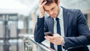 Oroad man läser SMS.