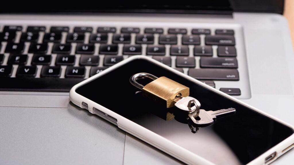Mobiltelefon och hänglås ovanpå dator