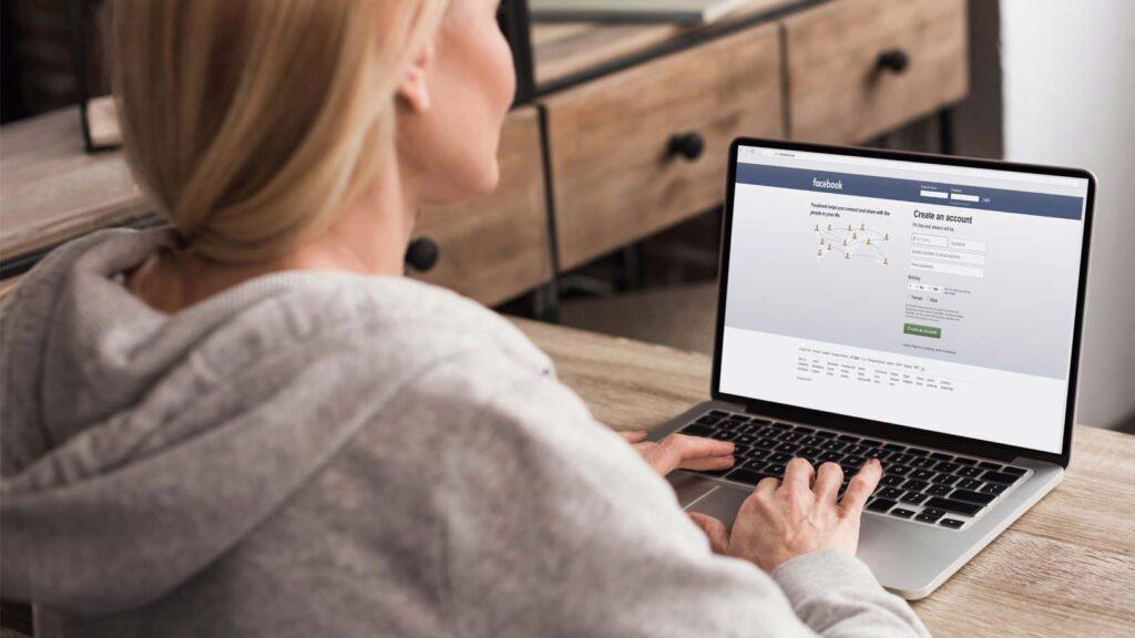 Kvinna med Facebook på laptop