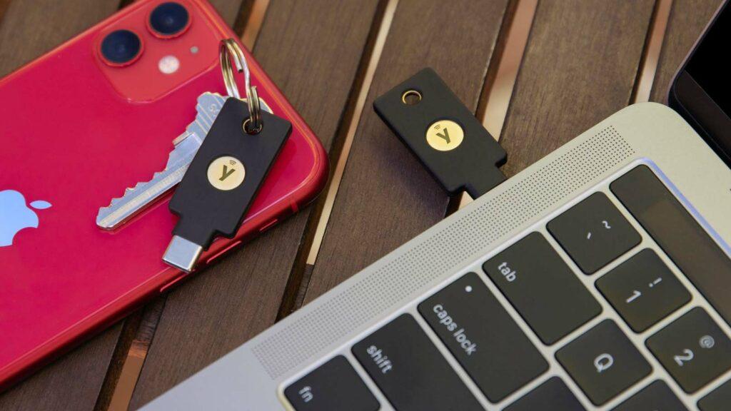 Två säkerhetsnycklar bredvid en Iphone och en Macbook Pro