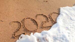 Havet spolar bort siffrorna 2020 från sandstranden.