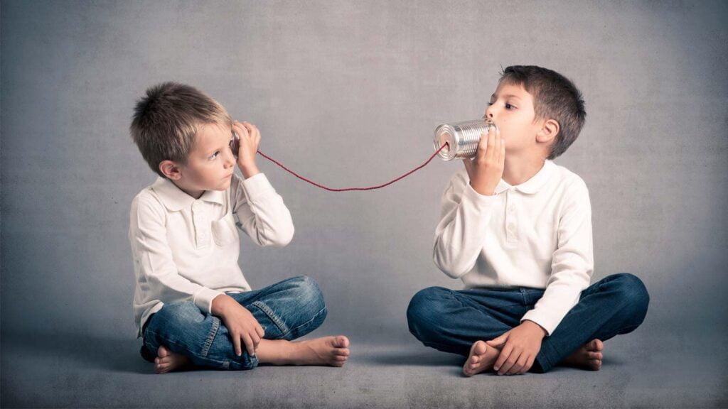 Två barn som pratar via burktelefoner.