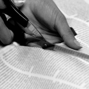 Någon klipper ut text ur tidning.