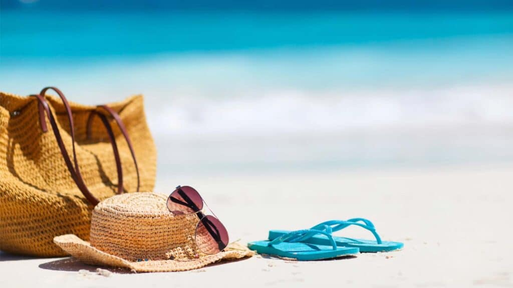 Hatt och sandaler på sandstrand