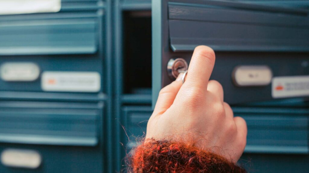 Hand låser upp brevlåda i flerbostadshus.