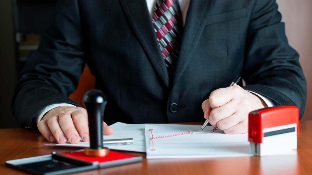 Man i kostym signerar och stämplar papper.
