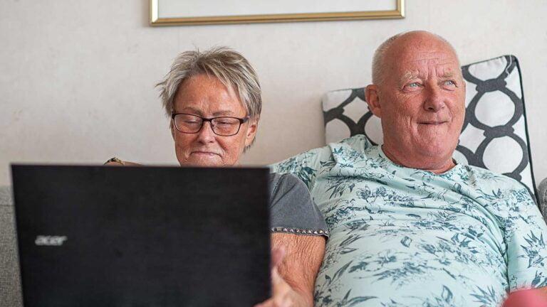 Två seniorer sitter i soffa med en bärbar dator framför sig.