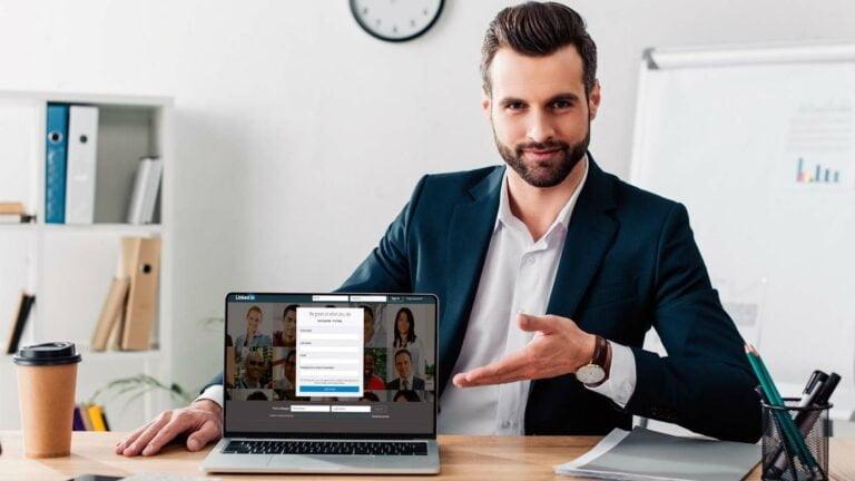 Man i kostym visar Linkedin på bärbar dator.