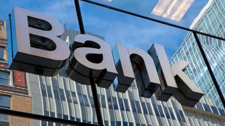 """Modern glasbyggnad med skylt där det står """"bank""""."""
