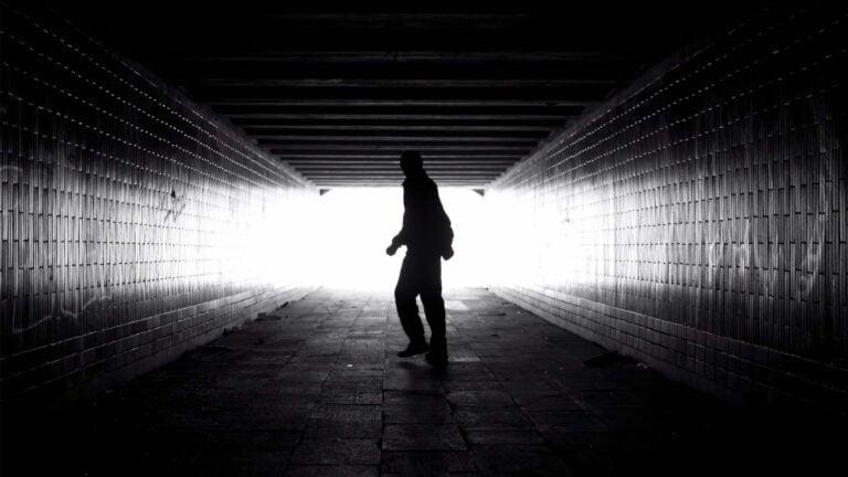 Person vänder sig om i en mörk tunnel.